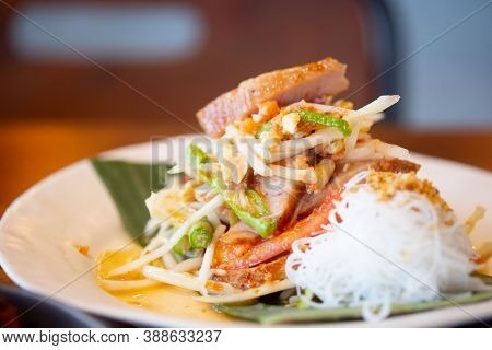 Close Up View Of Thai Spicy Green Papaya Salad Or Somtum Mix With Grilled Pork Neck Served With Rice