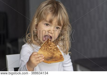 Little Girl Eating Pizza In The Kitchen, Sitting At The Table. Dessert For The Child.5.