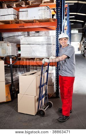 Portrait of warehouse worker with handtruck loading cardboard boxes at warehouse
