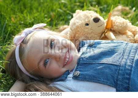 Pretty Little Child Girl Laying Down With Her Teddy Bear Toy On Blanket On Green Grass In Summer Smi