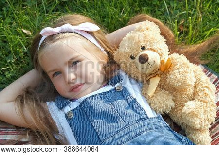 Pretty Little Child Girl Laying Down With Her Teddy Bear Toy On Blanket On Green Grass In Summer.
