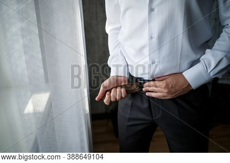 Elegant Businessman Man Fastening A Belt On His Trousers He Is Wearing A White Dress Shirt