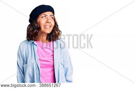Young beautiful mixed race woman wearing french look with beret looking away to side with smile on face, natural expression. laughing confident.