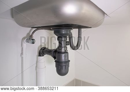 Pipe Under Kitchen Sink. Consist Of Stainless Steel, Concrete Counter, Pvc Plastic Pipe, Faucet, Tra
