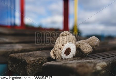 Lost Teddy Bear Lying On Wooden Bridge At Playground In Gloomy Day, Lonely And Sad Face Brown Bear D