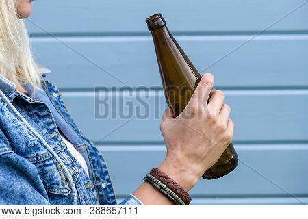 Woman Dressed Punk, Infirmal Holding A Bottle Of Beer Against Blue Wooden Plank Wall, Abuse And Fema