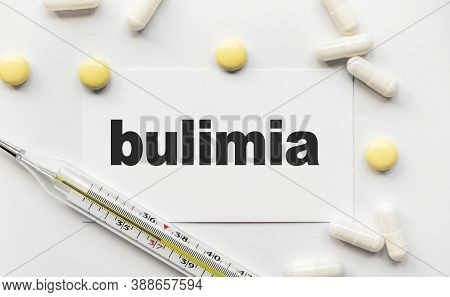 On White Business Card The Inscription Bulimia In Black Letters. Near Tablets And Capsules. Thermome