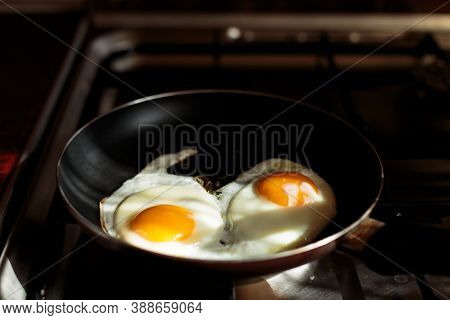 Making English Breakfast. Cooking Scrambled Eggs. Two Broken Eggs In A Frying Pan On The Stove. Two