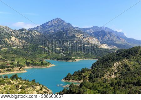 Reservoir At The Foot Of High Mountains. Green Mountains And Blue Water In The Reservoir.