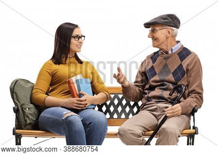 Young female student listening to an elderly man and sitting on a bench isolated on white background