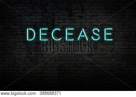 Neon Sign With Inscription Decease Against Brick Wall. Night View