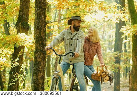 Couple In Love Ride Bicycle Together In Forest Park. Romantic Date With Bicycle. Bearded Man And Wom