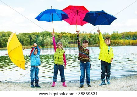 Kids in autumn clothing holding colorful umbrellas