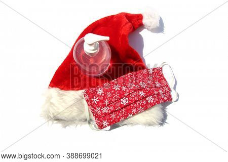 Coronavirus Christmas. Santa Claus Hat with Face Mask and Hand Sanitizer. Covid-19 Christmas. Covid-19 Face Mask with Santa Hat and Hand Sanitizer. Coronavirus is dangerous be safe.