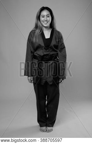 Portrait Of Happy Young Asian Woman Wearing Karate Gi Ready To Fight
