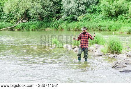 Its Engaging For Life. Mature Man Fly Fishing. Man Catching Fish. Fisherman Show Fishing Technique U