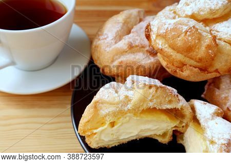 Delectable French Cream Puffs  Served On Wooden Table With A Cup Of Hot Tea