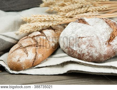 Assortment Of Baked Bread  And Wheat On The Wooden