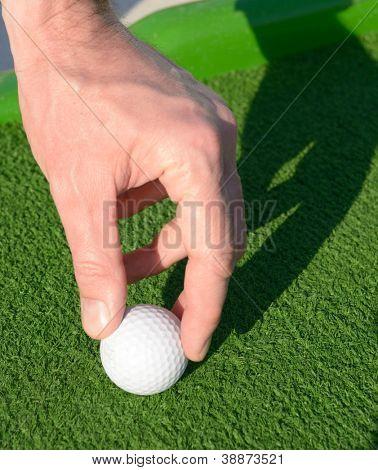 Man setting up a minigolf ball on a golf course