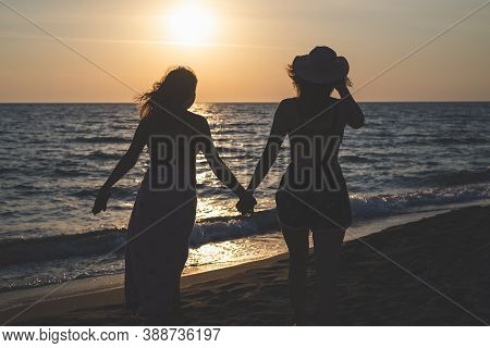 Gay Couple On Beach In Sunset. People In Vacation. Gay Girl Couple On Beach In Vacation In Sunset. P