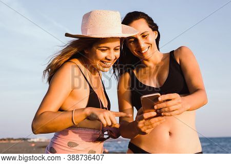 Girls On Beach With Cell Phone. Two Girls Portrait With Cell Phone On Beach In Sunset. Girls Looking