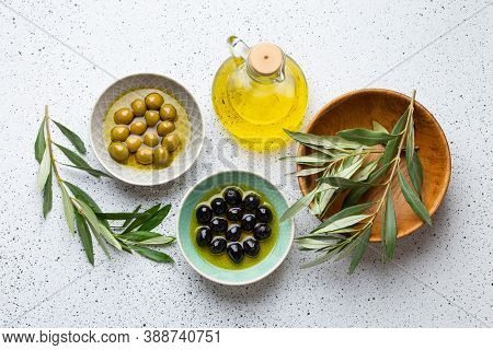 Green And Black Olives With Olive Oil In A Glass Bottle, Olive Tree Sprigs And Cut Fresh Ciabatta Br