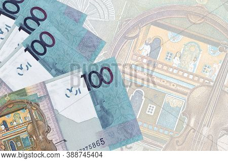 100 Belorussian Rubles Bills Lies In Stack On Background Of Big Semi-transparent Banknote. Abstract