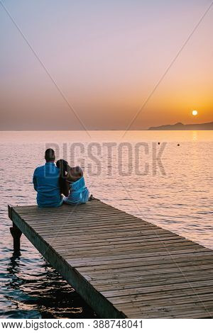 Crete Greece, Young Romantic Couple In Love Is Sitting And Hugging On Wooden Pier At The Beach In Su