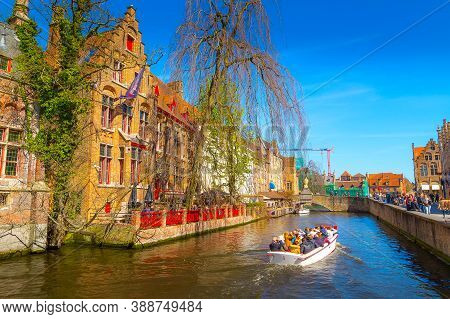 Bruges, Belgium - April 10, 2016: Scenic Cityscape With Medieval Houses, Boat With Tourists And Cana