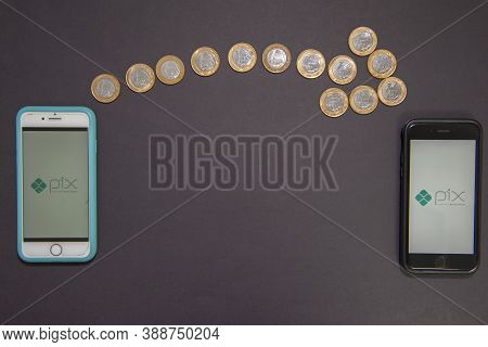 Florianopolis, Brazil. 10/07/2020: PIX logo on the smartphone screen next to dollar sign made by 1 Real coins on black background. New instant payment system. Copy space.