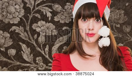 confused woman wearing a christmas hat against a vintage background