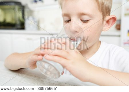 A Little Boy In The Kitchen Drinks Clean Water From A Glass, Clean Water Is A Pledge Of Health