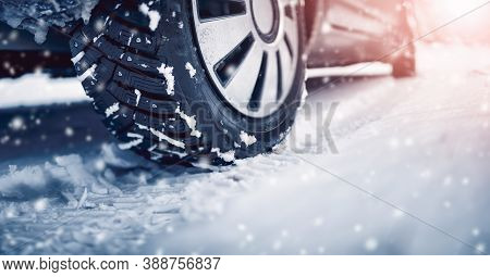 Closeup Of The Car Tire On Winter Road Covered With Snow In Snowfall In Sunny Day