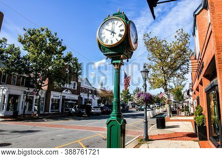 NEW CANAAN, CT, USA - OCTOBER 4, 2020: Downtown in nice day with clock, store fronts, restaurant and blue sky on Elm Street