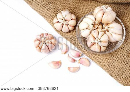 Garlic Cloves And Bulb In Glass Bowl On Hemp Sack. Garlic Bulbs On Rustic Old Table. Top View Fresh