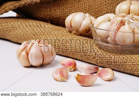 Garlic Cloves And Bulb In Glass Bowl On Hemp Sack. Garlic Bulbs On Rustic Old Table. Fresh Gralic Cl