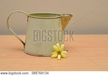 A Rusty Old Mug On A Table With A Yellow Daisy