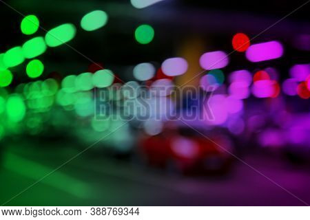 Blurred Cars In Car Parking Lot In Shopping Mall. Bokeh Lights Background. Abstract Blur Car Parking