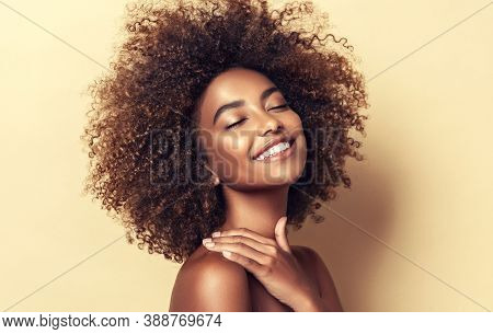 Beauty Portrait Of African American Woman With Clean Healthy Skin On Beige Background. Smiling Dream