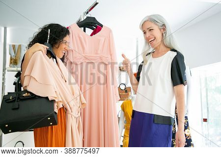 Happy Joyful Female Friends Shopping Together And Discussing Chosen Dress In Fashion Store. Seller A