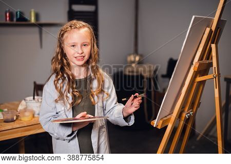 A Little Girl Painter Poses And Smiles At The Camera Near Her Painting In The Artists Studio