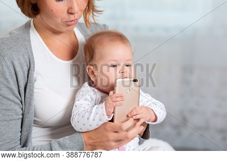 A Mother Holds The Baby In Her Arms And Gives Him A Smartphone, Hes Trying To Eat. Concept Of Learni