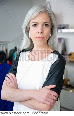 Serious Caucasian Fair Haired Woman Standing With Arms Folded Near Rack With Dresses In Clothes Shop