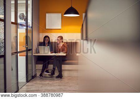 Two Businesswomen Working Late In Open Plan Office Using Laptop