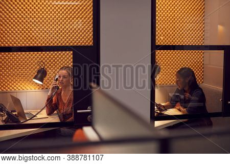 Businesswomen Working Late In Individual Office Cubicles Using Laptop And Digital Tablet
