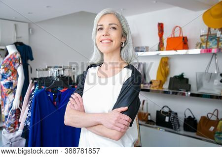 Cheerful Caucasian Fair Haired Woman Standing With Arms Folded Near Rack With Dresses In Clothes Sho