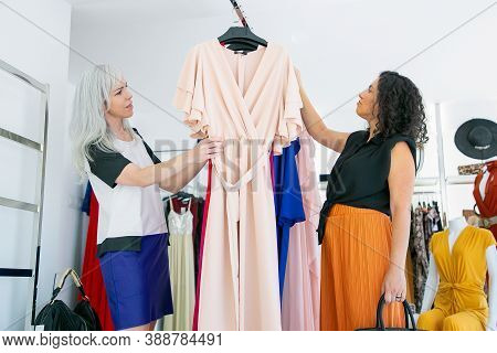 Pensive Customer And Shop Seller Browsing Dresses On Rack Together, Choosing Clothes In Fashion Stor