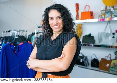 Joyful Latin Black Haired Woman Standing With Arms Folded Near Rack With Dresses In Clothes Shop, Lo