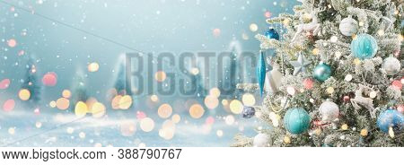 Christmas Tree with Decoration On A Winter Background With Bright Lights And Snow