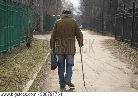 An Elderly Man With A Stick Is Walking Down The Street. A Man Aged. The Old Grandfather Is Walking.
